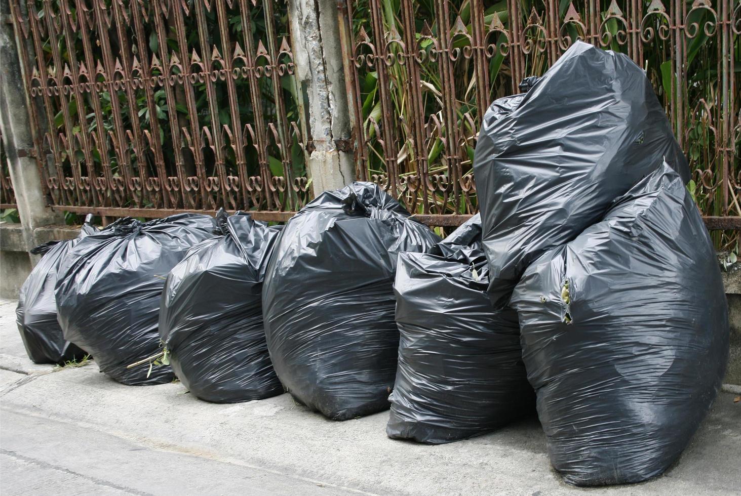 fila di sacchi della spazzatura all'esterno foto