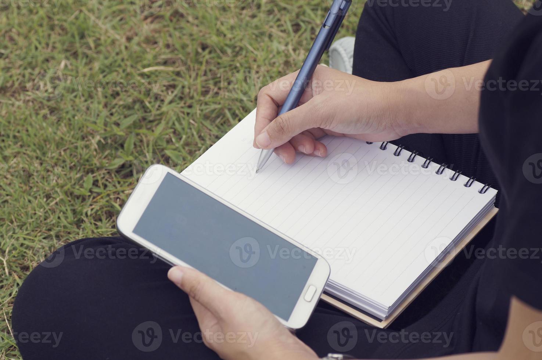 mano della donna che scrive su carta e usa il telefono foto