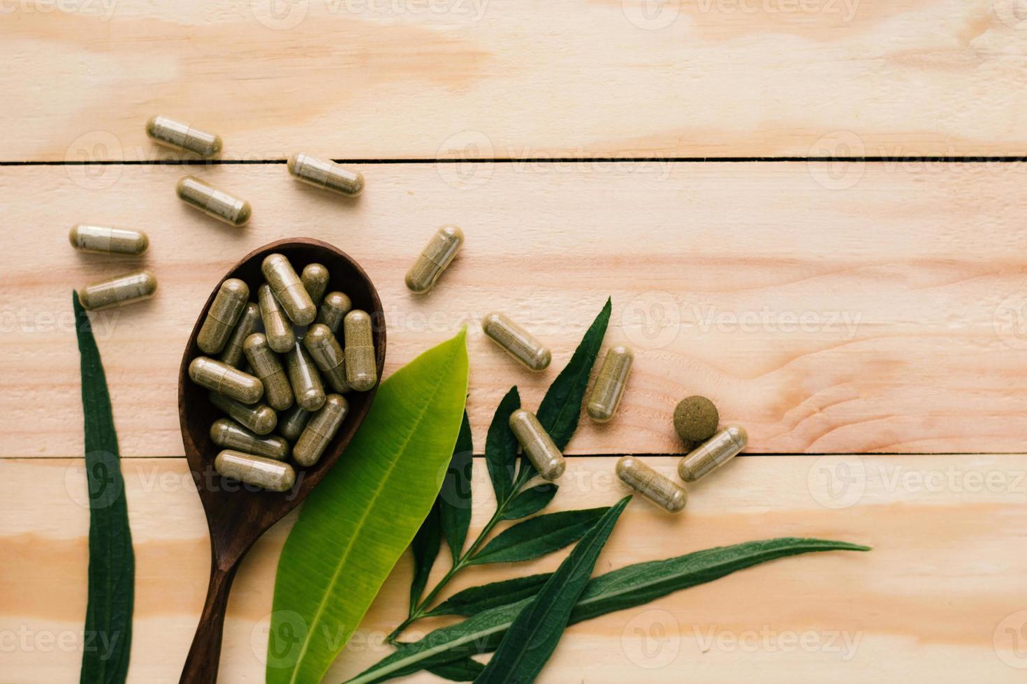 vista dall'alto del farmaco a base di erbe e bottiglia su uno sfondo di legno foto