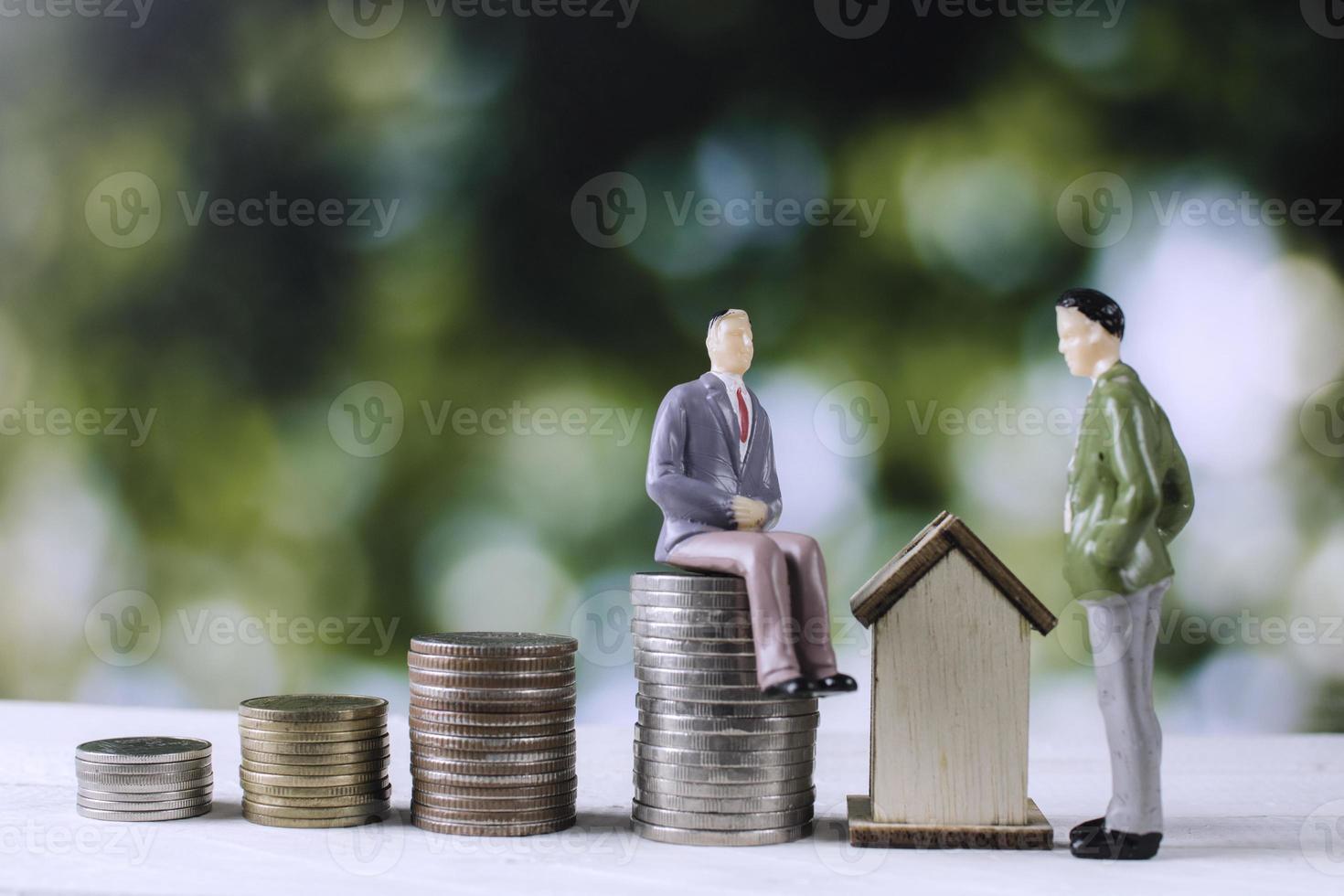 modello di uomini d'affari con denaro monete e casa foto