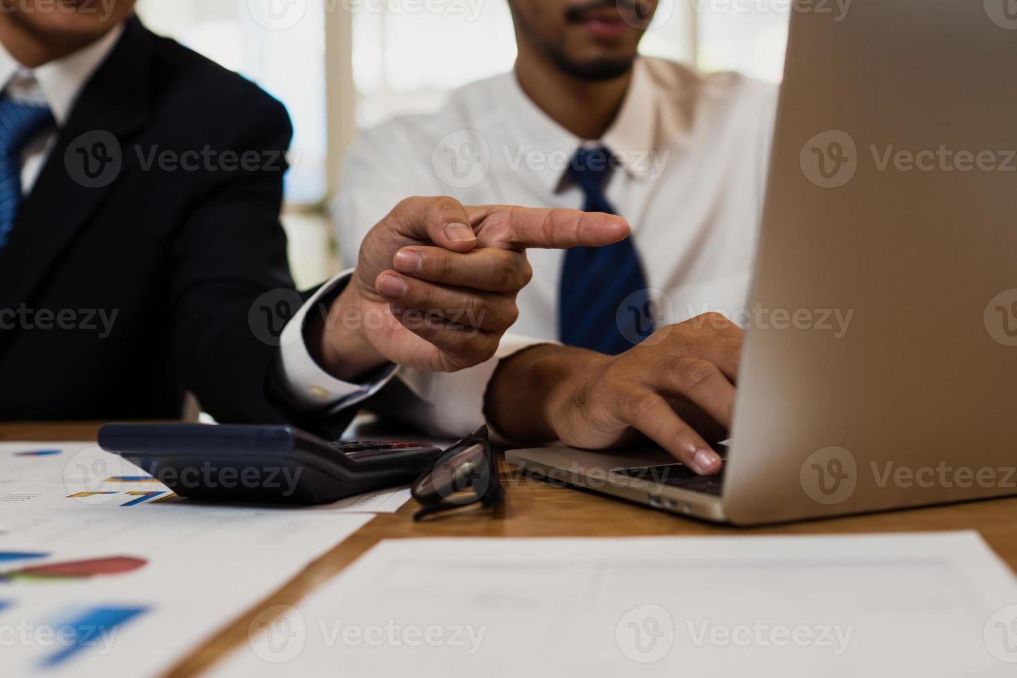 uomo che punta allo schermo di un computer foto