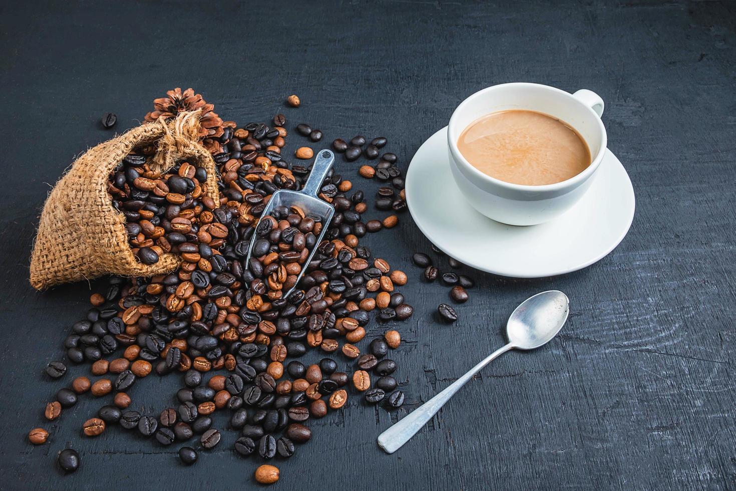 tazza di caffè con chicchi di caffè su uno sfondo scuro foto