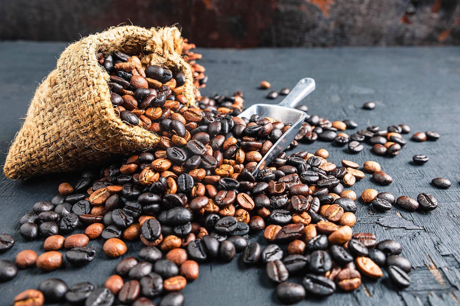 chicchi di caffè in un sacchetto di stoffa marrone foto