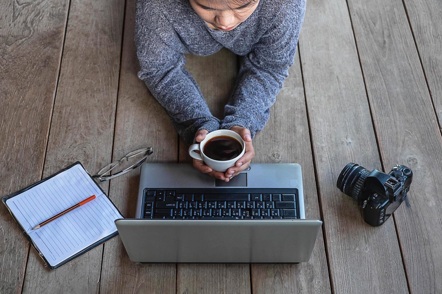 donna posa sul pavimento lavorando su un computer portatile foto