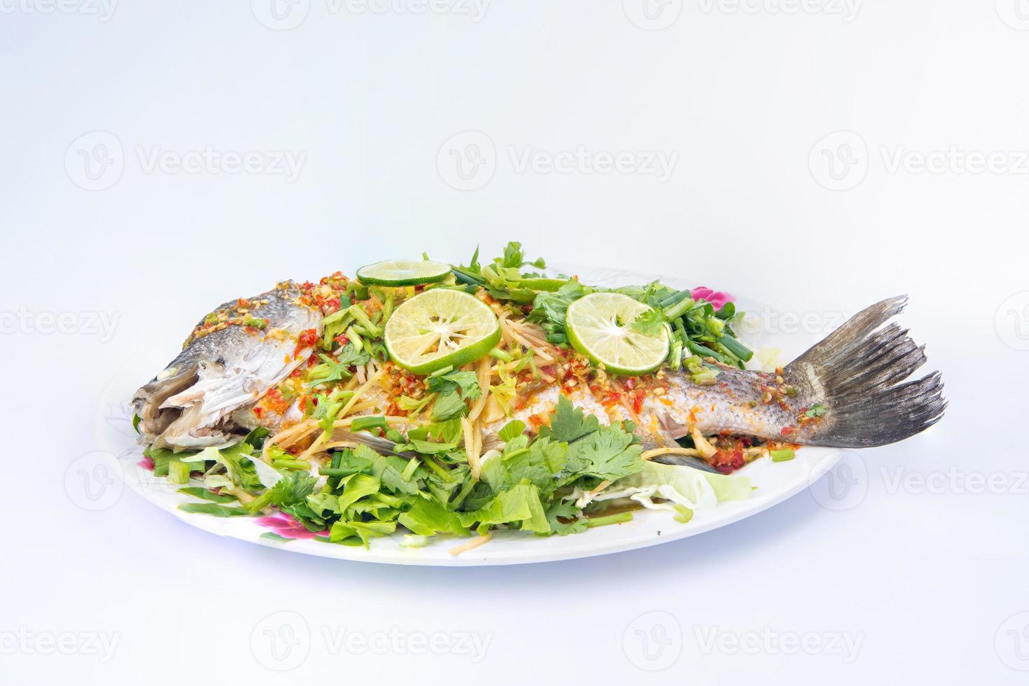 branzino al vapore al limone sul piatto isolato su sfondo bianco foto