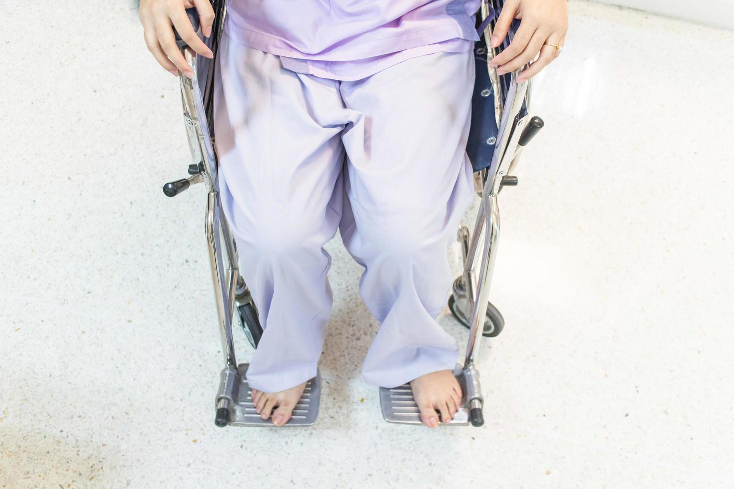 paziente donna in sedia a rotelle seduto in un corridoio dell'ospedale foto