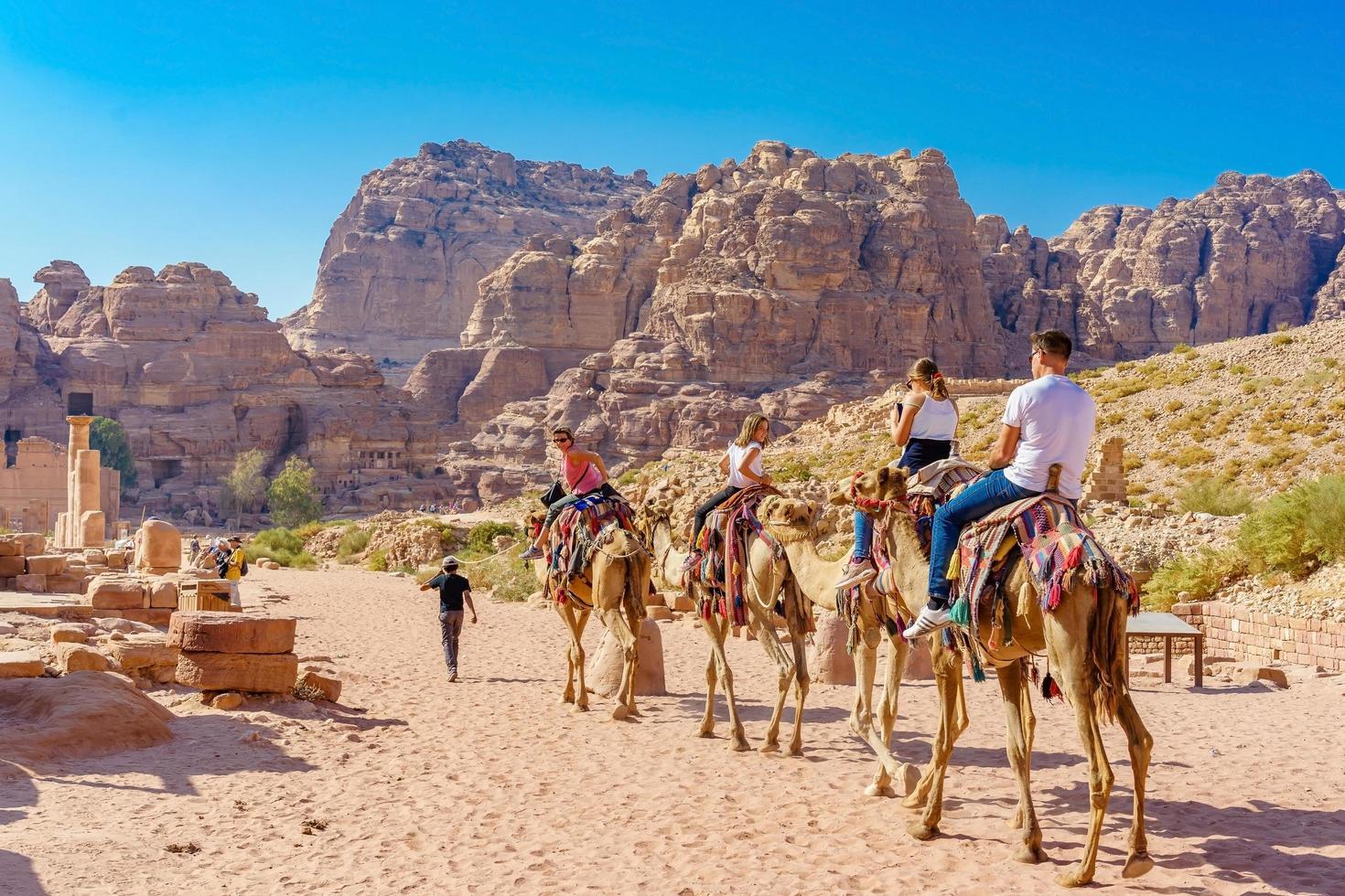 I turisti a cavallo di cammelli a petra, giordania, 2018 foto