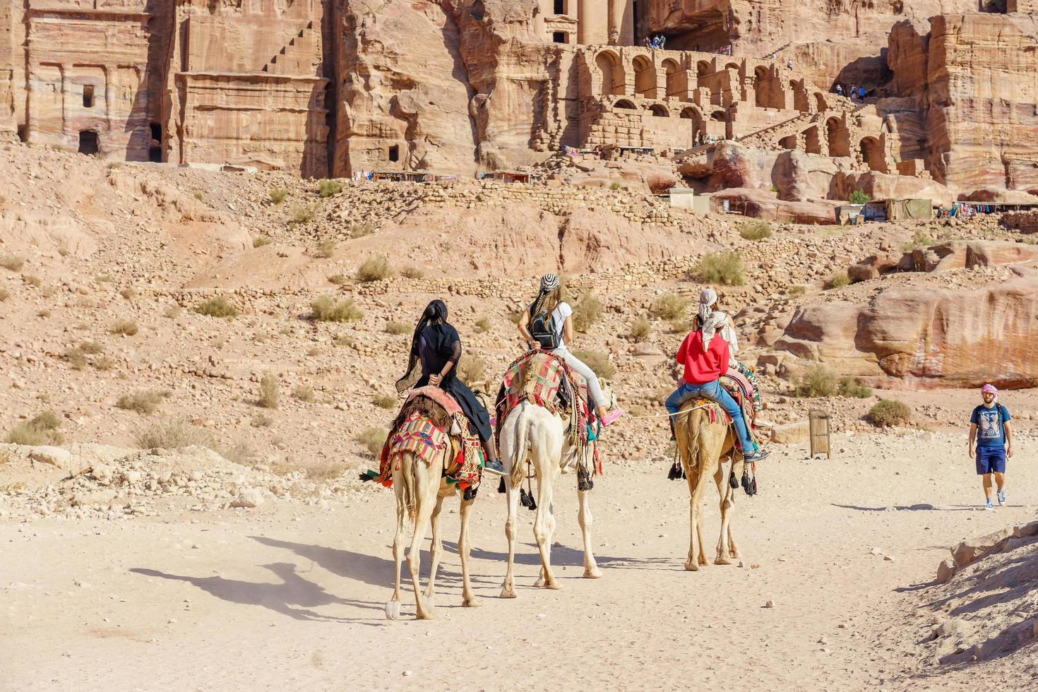 I turisti a cavallo di cammelli a Petra, in Giordania, 2018 foto