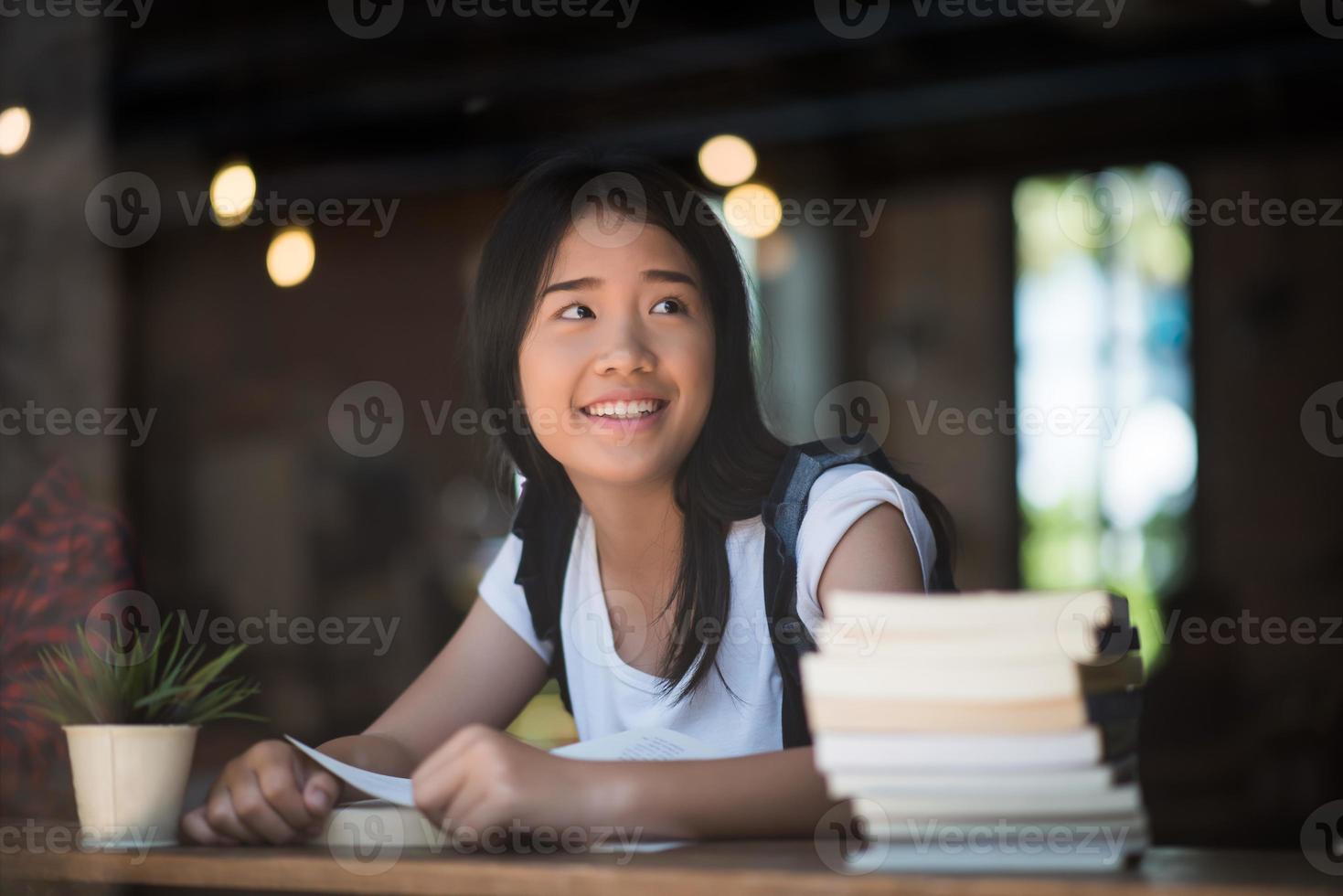 giovane donna che legge il libro seduto al chiuso in un caffè urbano foto