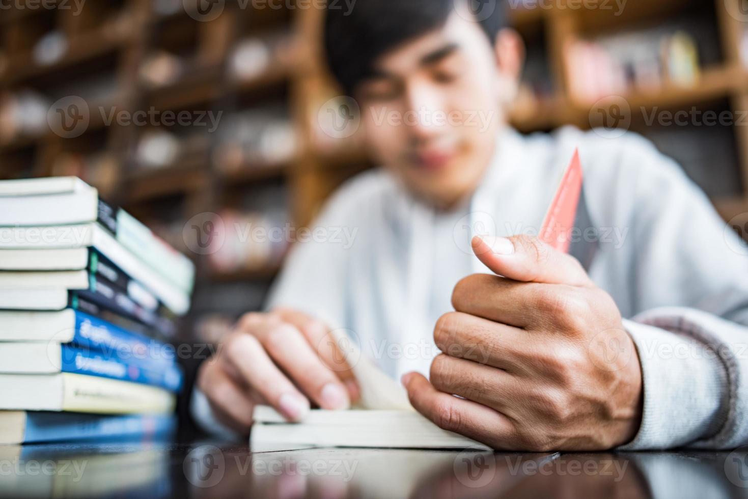 giovane studente che legge in un caffè foto