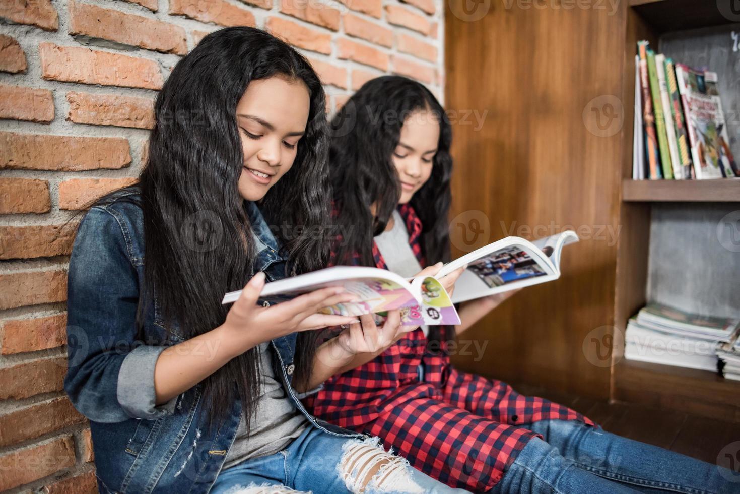 studentesse che leggono libri in biblioteca foto