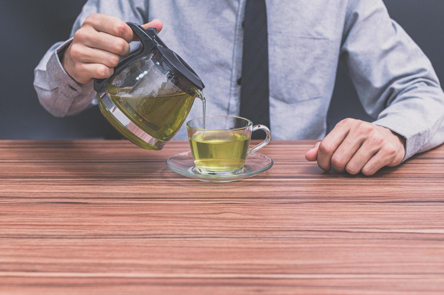 un uomo che versa una tazza di tè foto