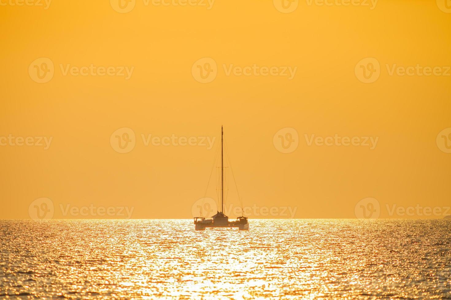 barca in acqua con un tramonto arancione foto