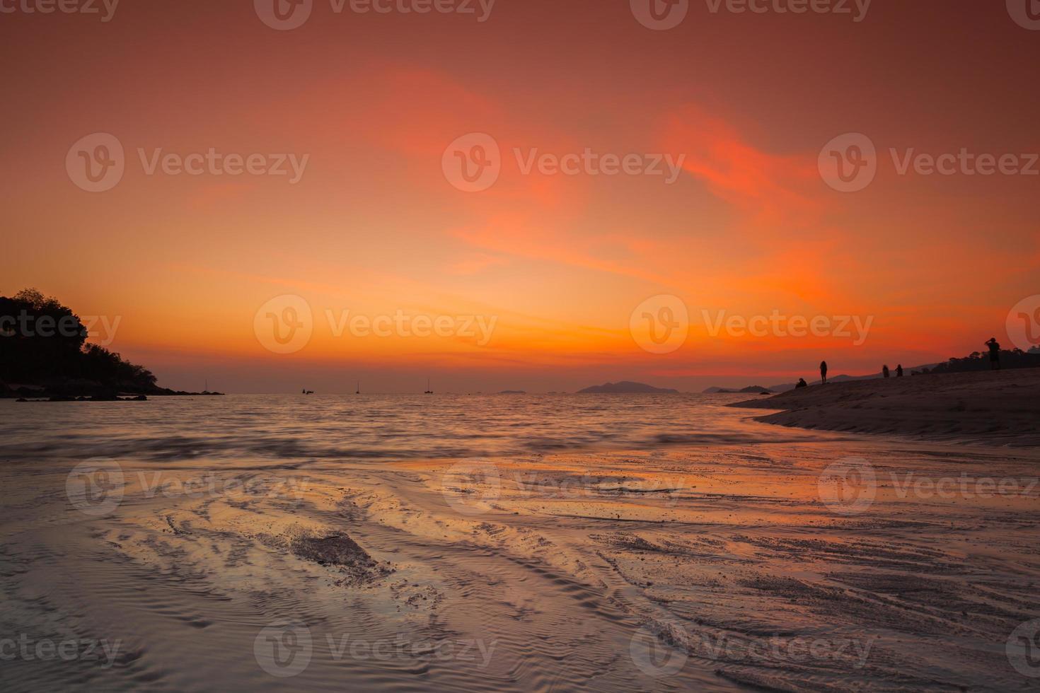 arancione tramonto sull'acqua in una spiaggia foto