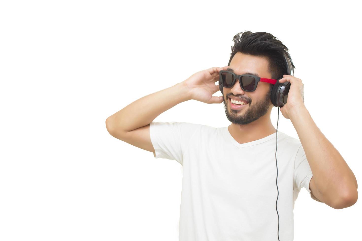 uomo asiatico che sorride e che ride ascolta la musica con le cuffie isolate su fondo bianco foto