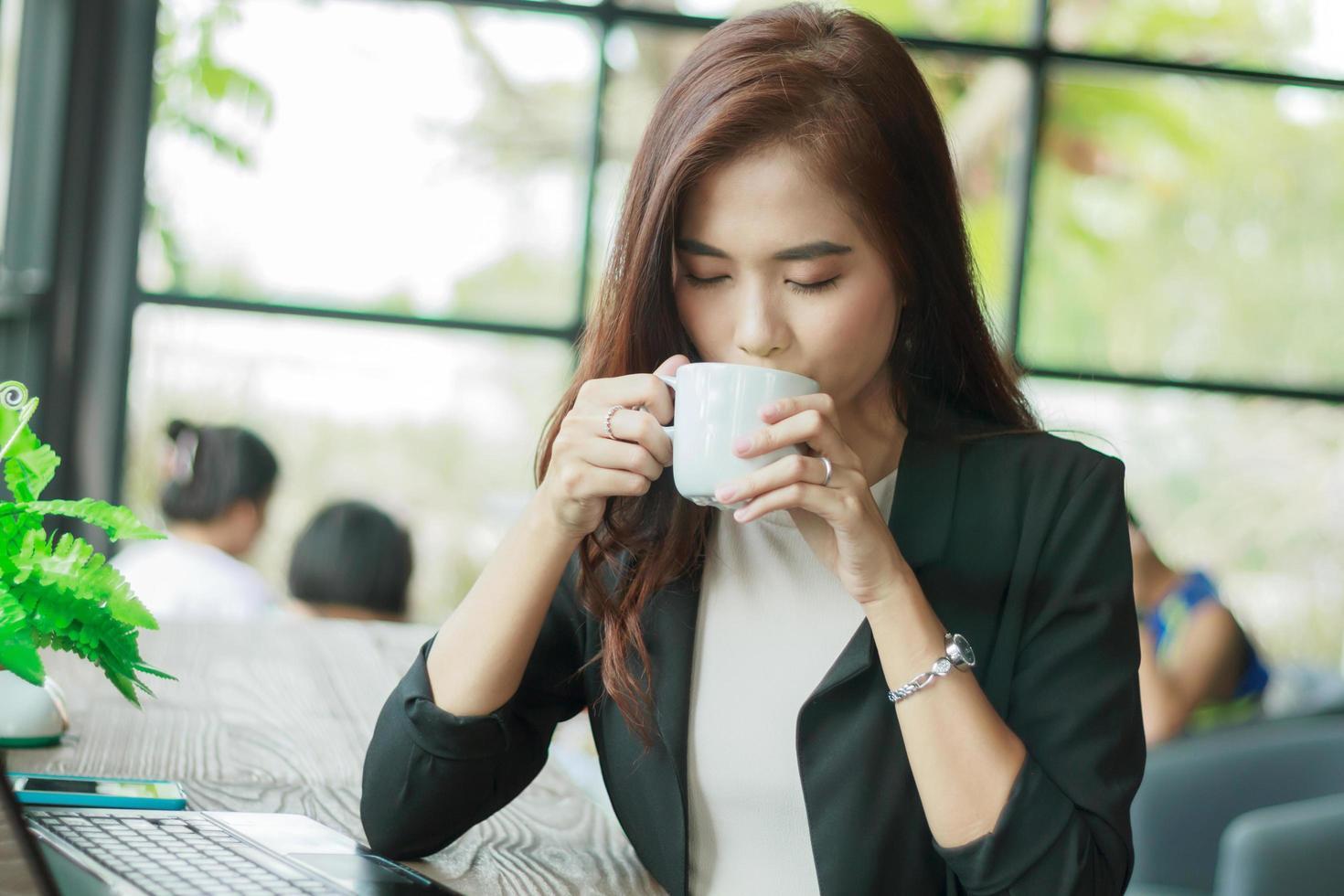 donna asiatica di affari che beve caffè foto