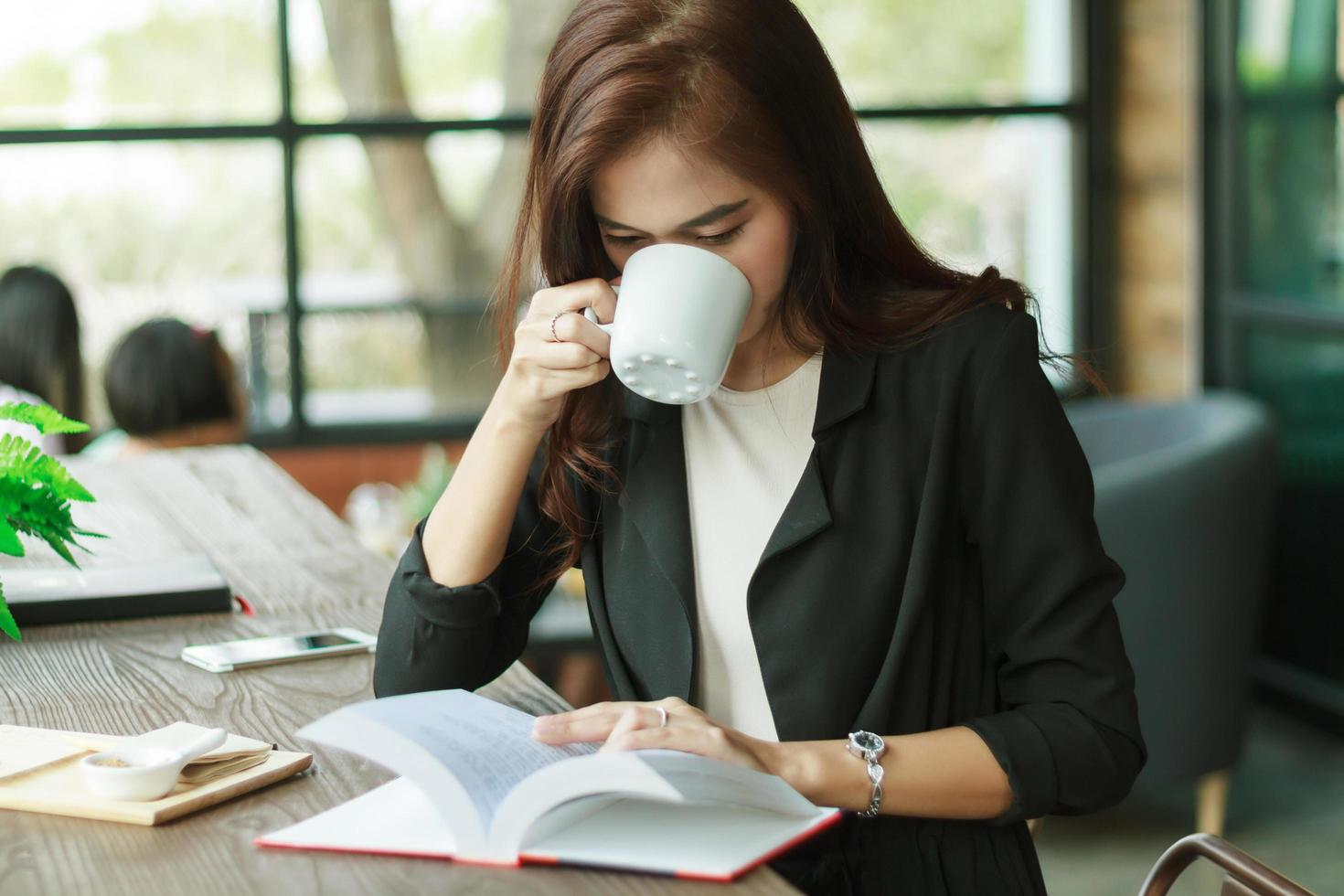 donna asiatica di affari che legge e che beve caffè foto