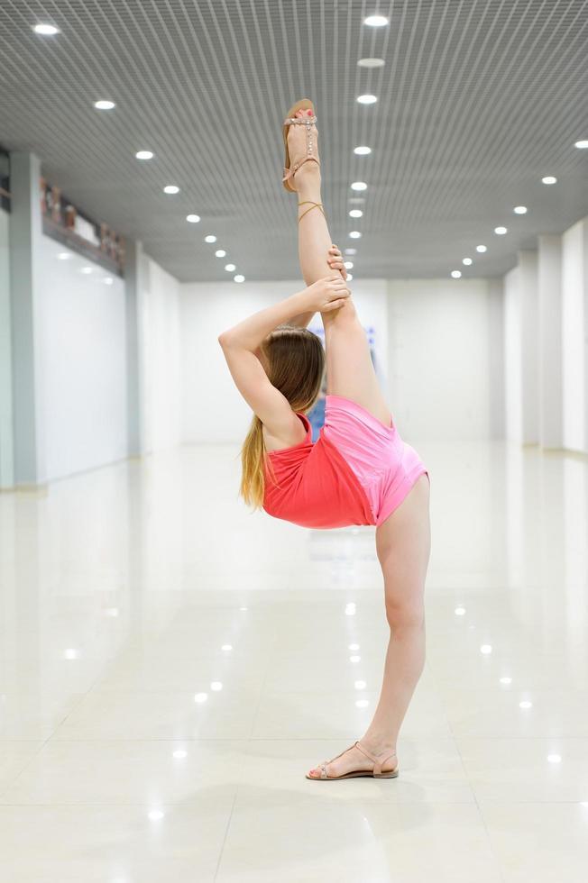ginnasta che fa una divisione verticale in una stanza luminosa foto