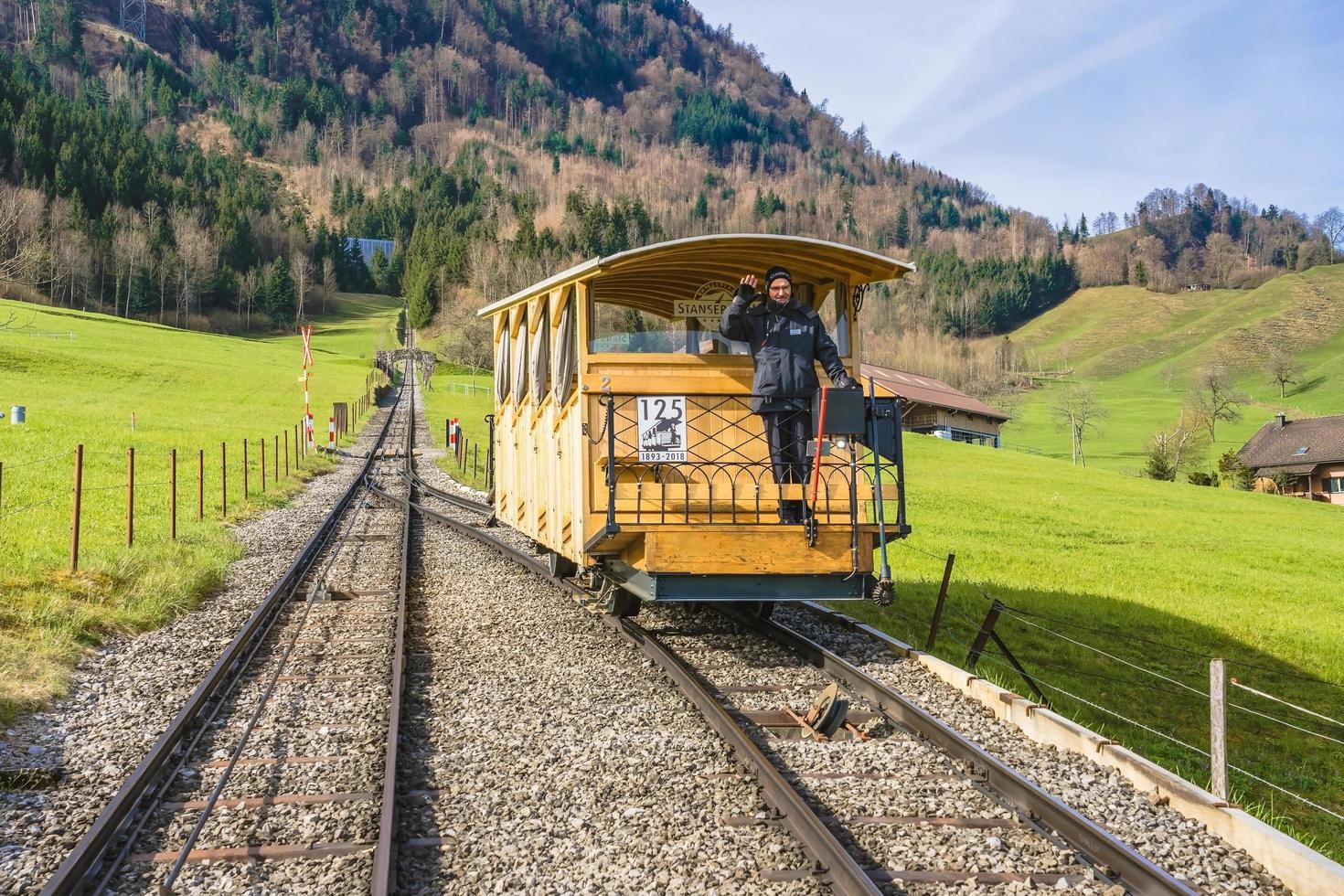 Un uomo sul vagone della funicolare Stanserhornbahn, Svizzera foto