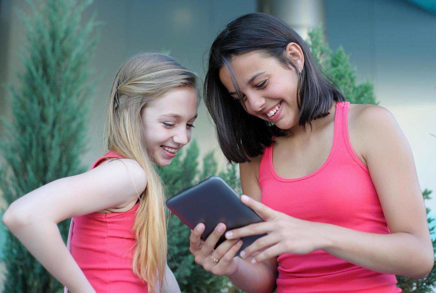 due ragazze che si divertono utilizzando un tablet foto