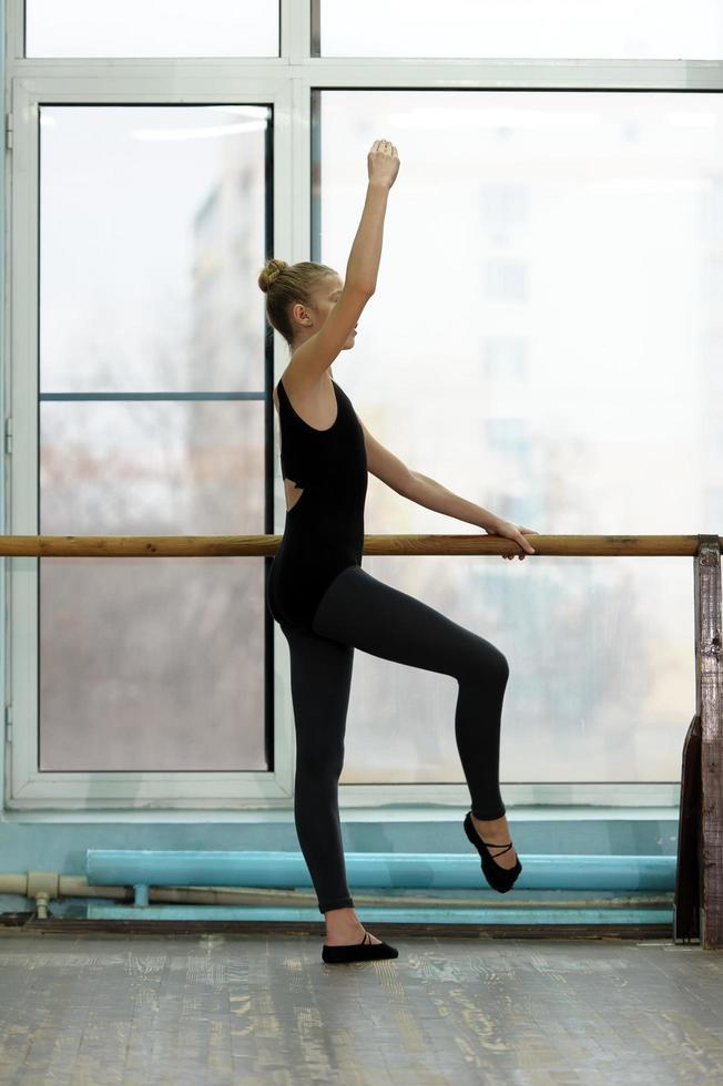 giovane ballerina che si esercita alla sbarra in studio foto