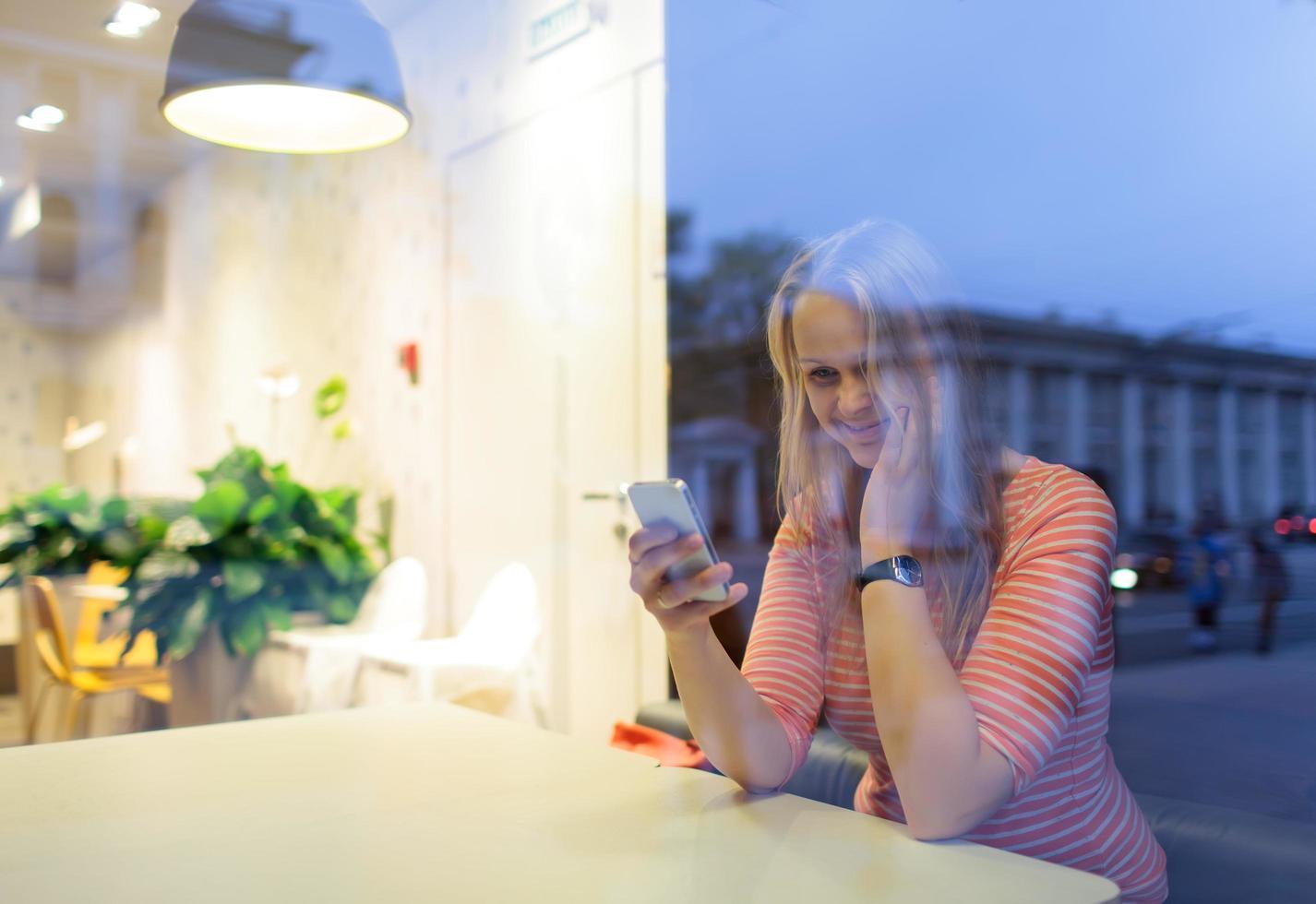 donna in un caffè utilizzando un telefono foto