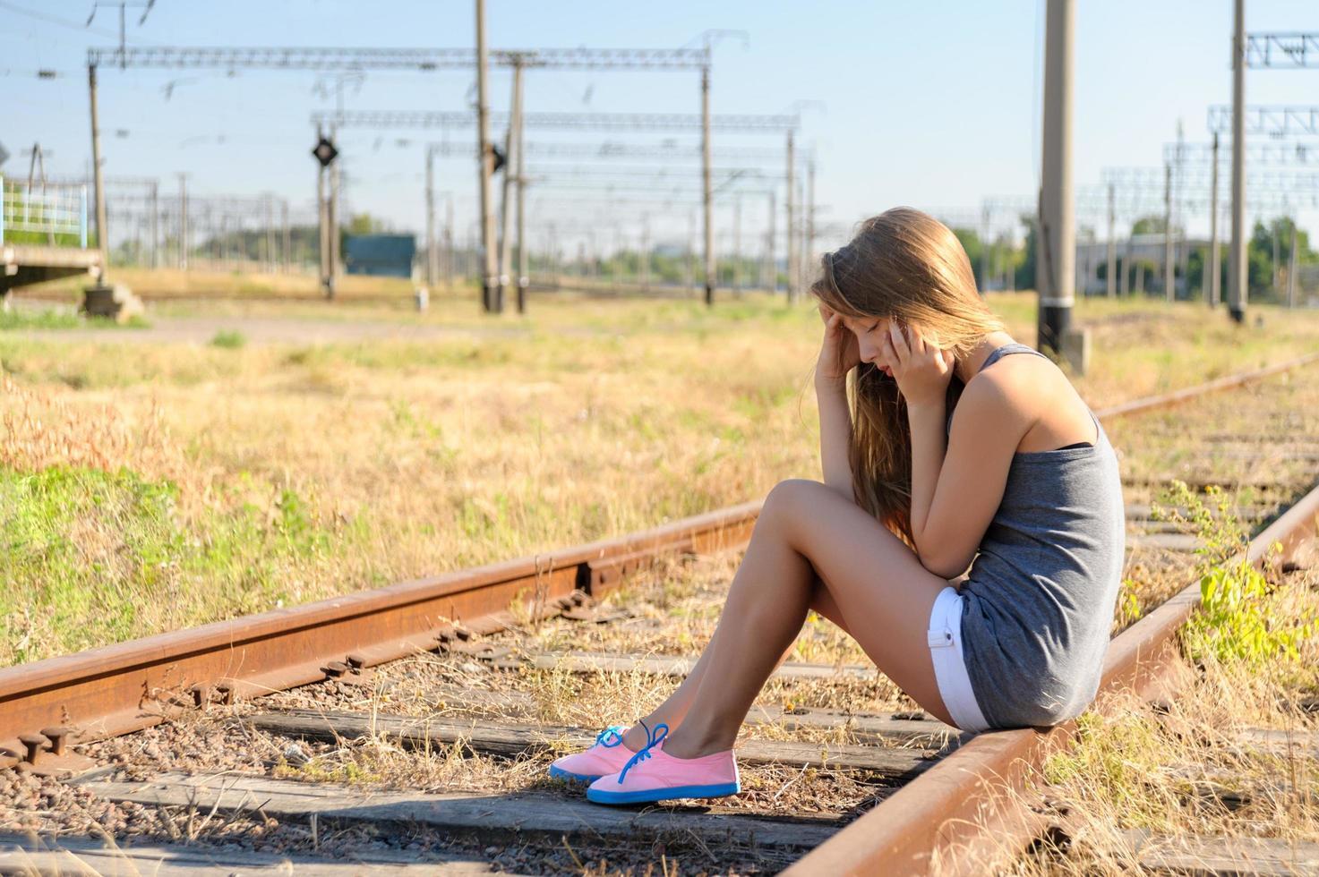 ragazza triste che si siede sui binari del treno foto