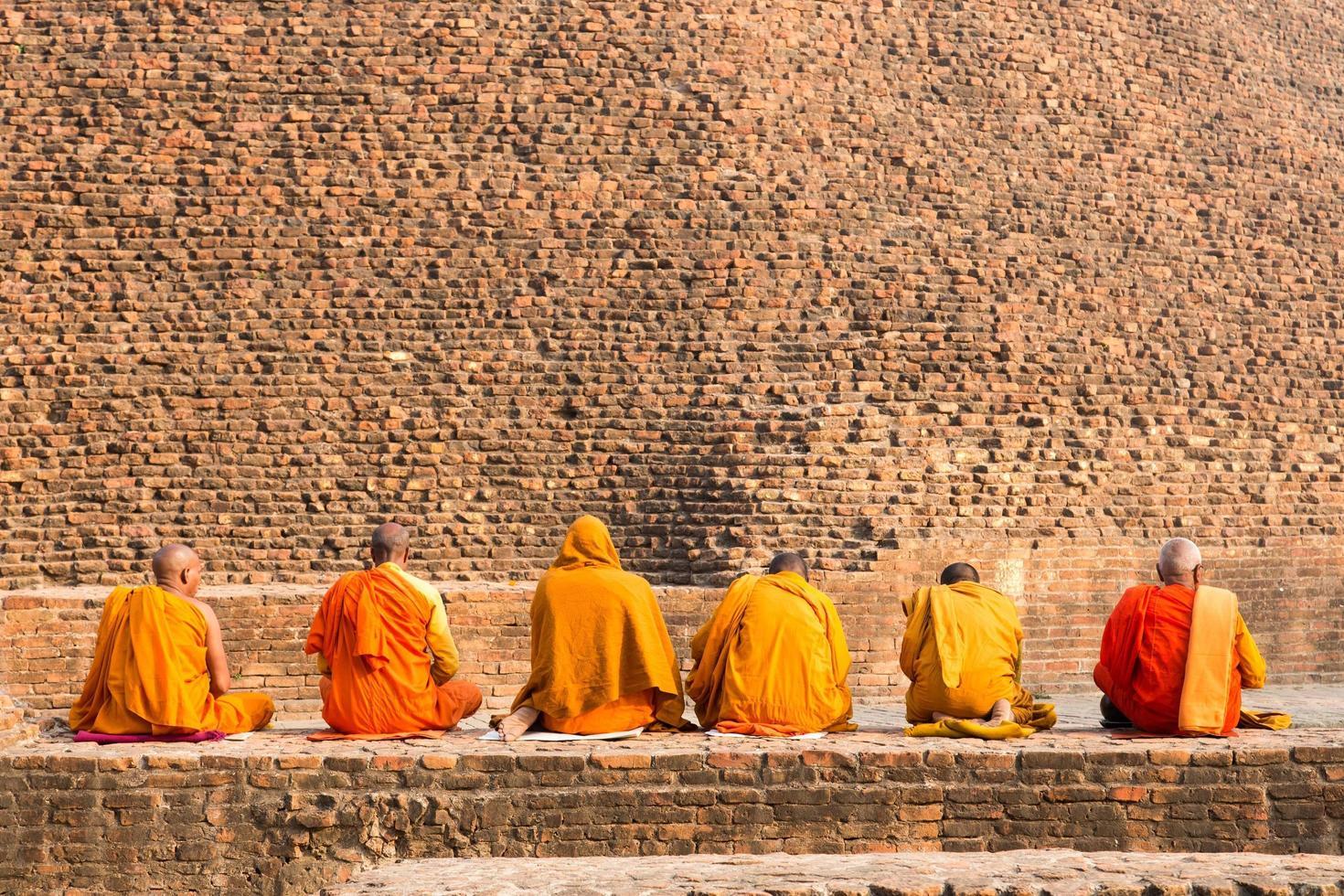 monaci buddisti seduti davanti al vecchio stupa nella città di kushiingar, india foto