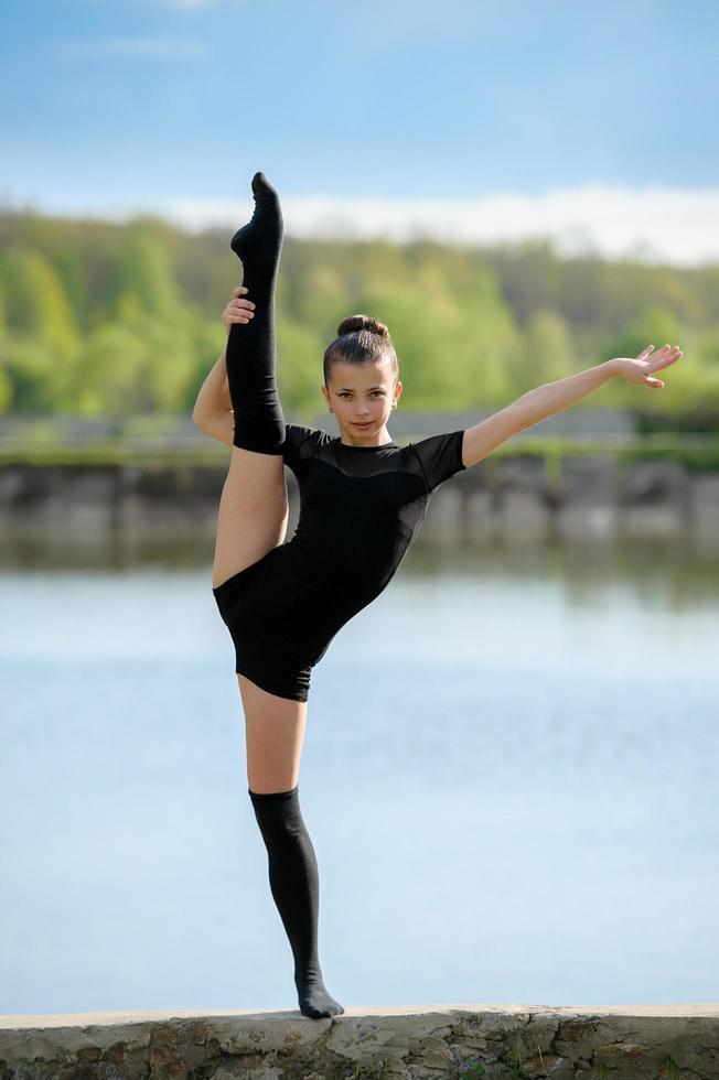 ginnasta ritmica che esegue una spaccatura verticale della gamba all'esterno foto