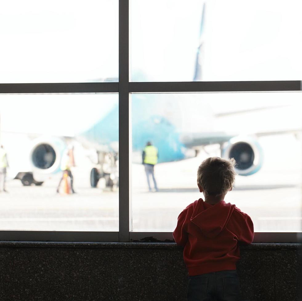 ragazzo che guarda l'aereo in aeroporto foto