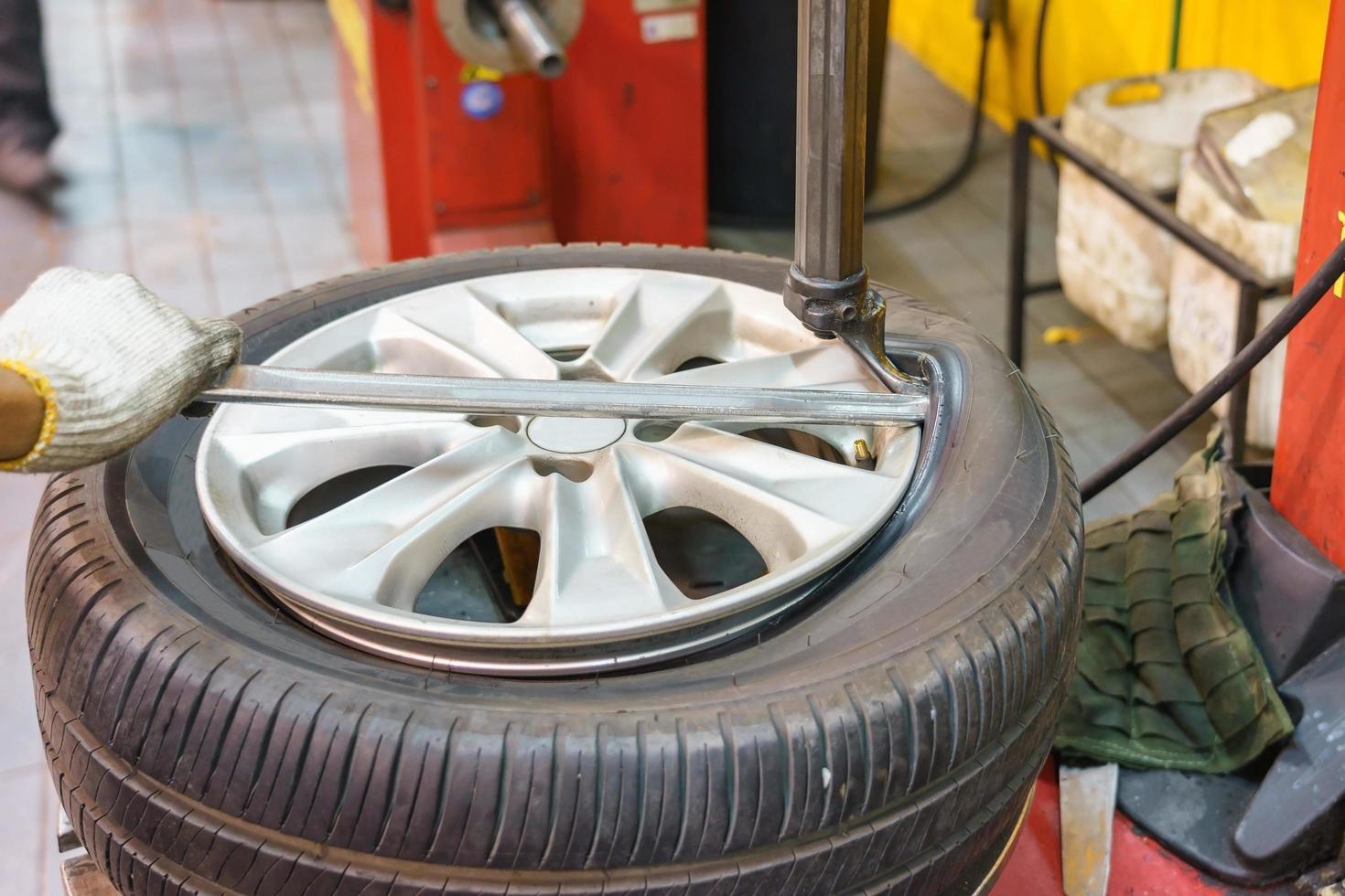 primo piano del meccanico cambiando pneumatici per auto in officina foto