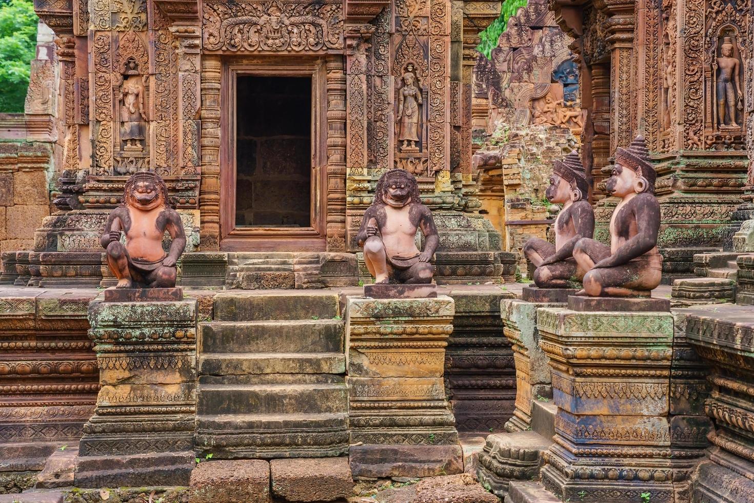 statue di leoni e scimmie al tempio di arenaria rossa di banteay srei, cambogia foto