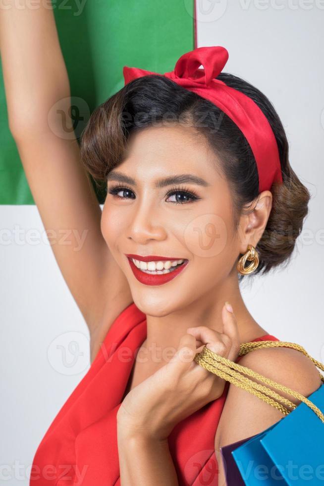 bella donna asiatica che tiene le borse della spesa colorate foto