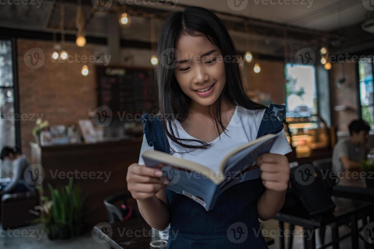 giovane donna che legge il libro seduto al chiuso in urban cafe foto