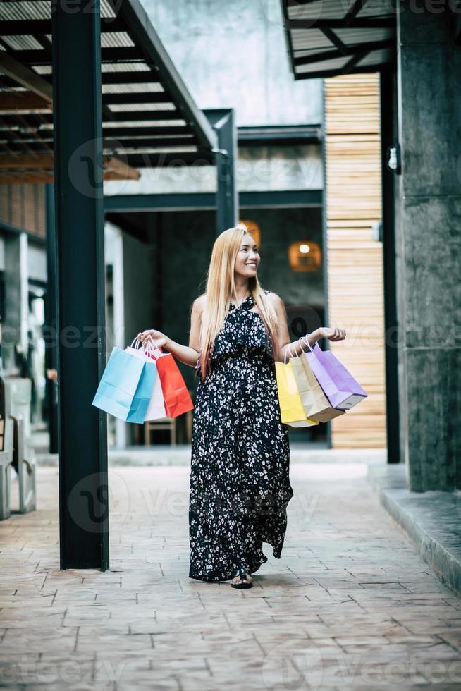 ritratto di una giovane donna felice con le borse della spesa a piedi per la strada foto