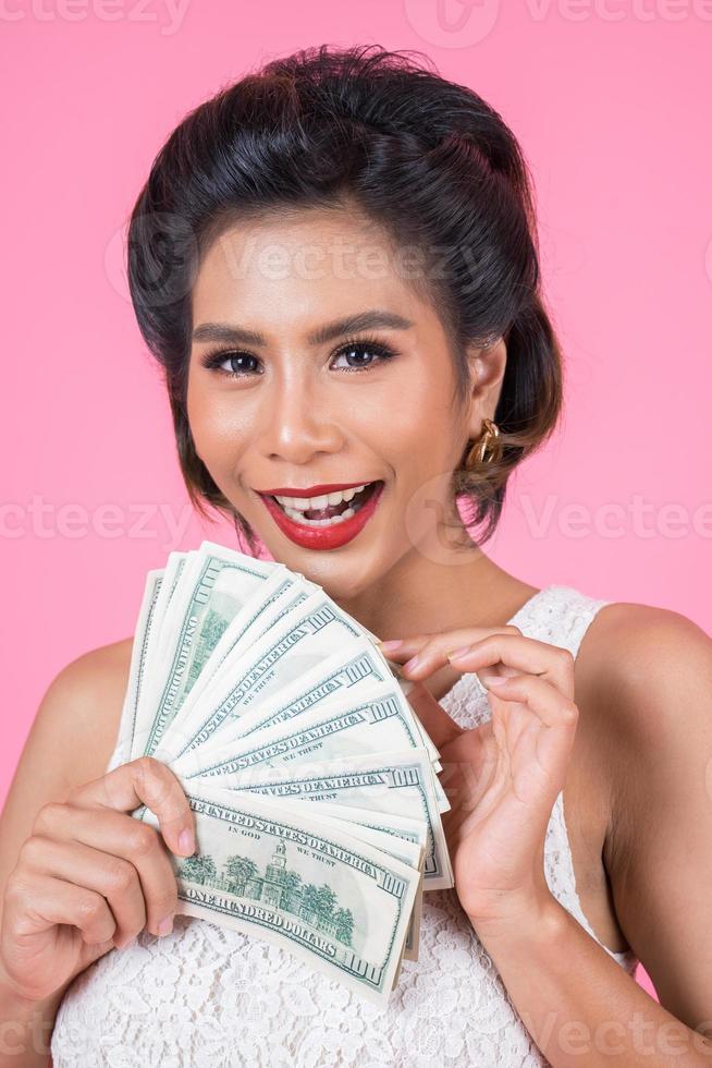 bella donna felice che tiene i dollari foto