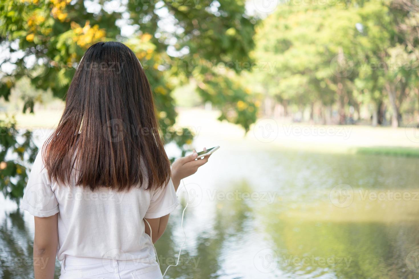 parte posteriore della giovane donna che si distende al parco foto