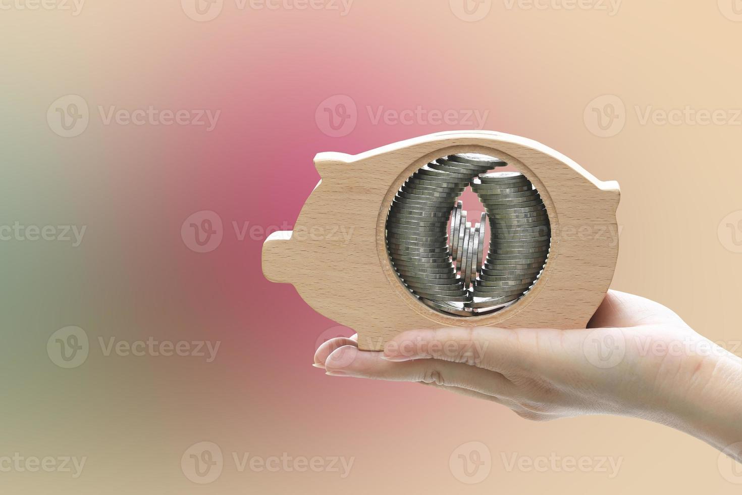 mano che tiene il salvadanaio con pile di monete impostate all'interno foto