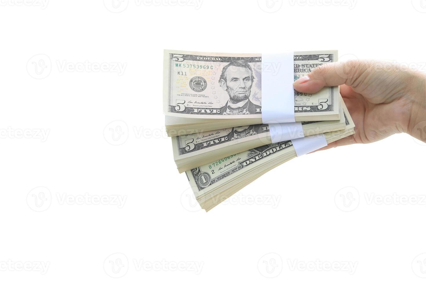 mano che regge pile di cinque dollari e un dollaro su sfondo bianco foto