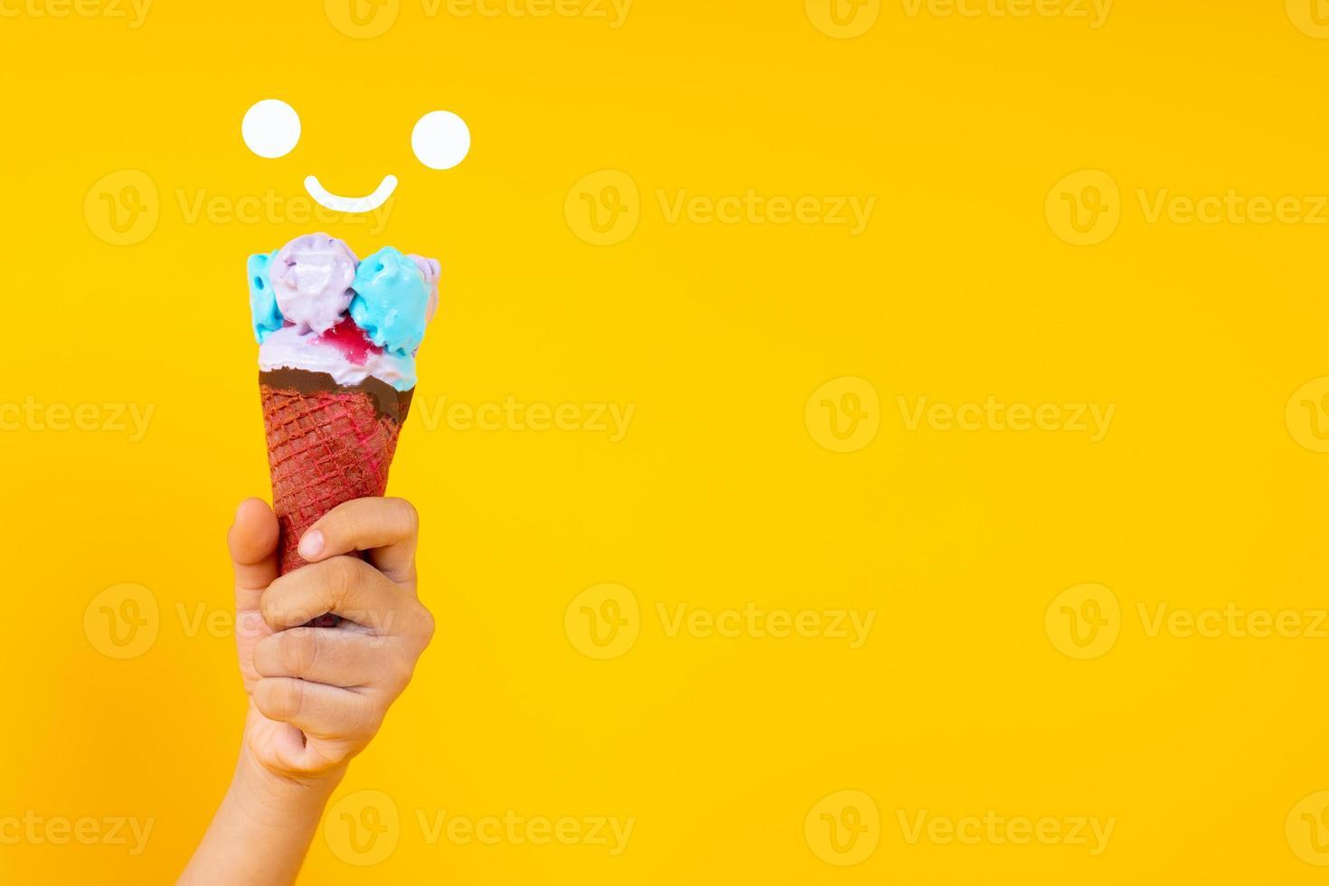 vicino la mano che tiene il cono gelato colorato su sfondo giallo foto