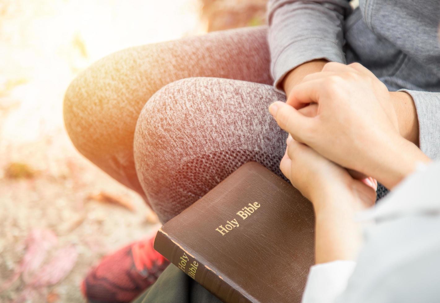 due donne che si tengono per mano e pregano mentre studiano la Bibbia foto