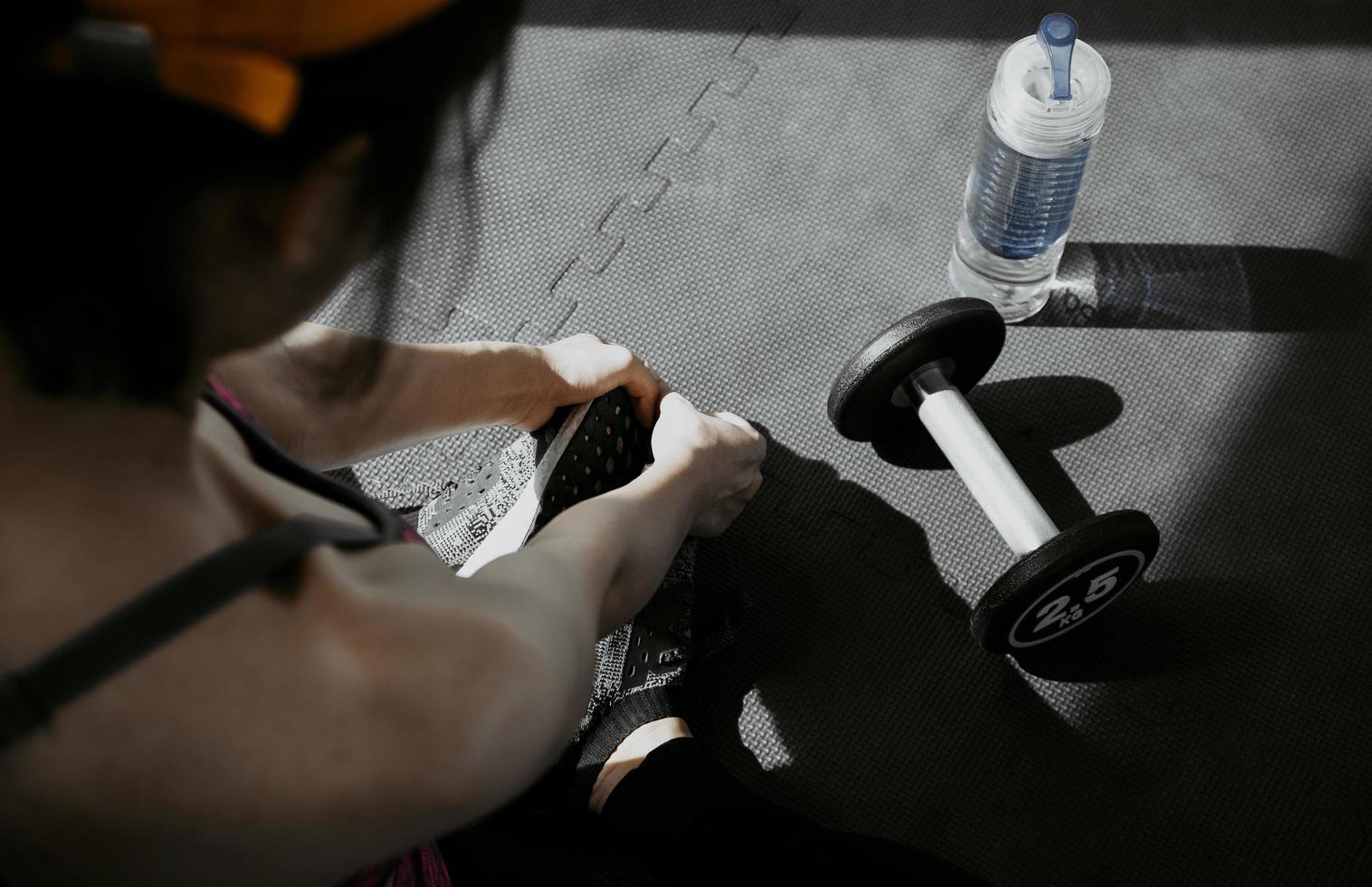 donna che lega i lacci delle scarpe. Close up del corridore di fitness sport femminile si prepara per fare jogging in palestra foto