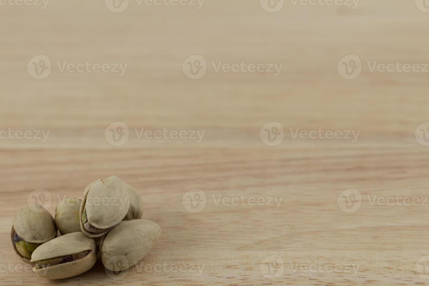 pistacchi isolati su un blocco di legno foto