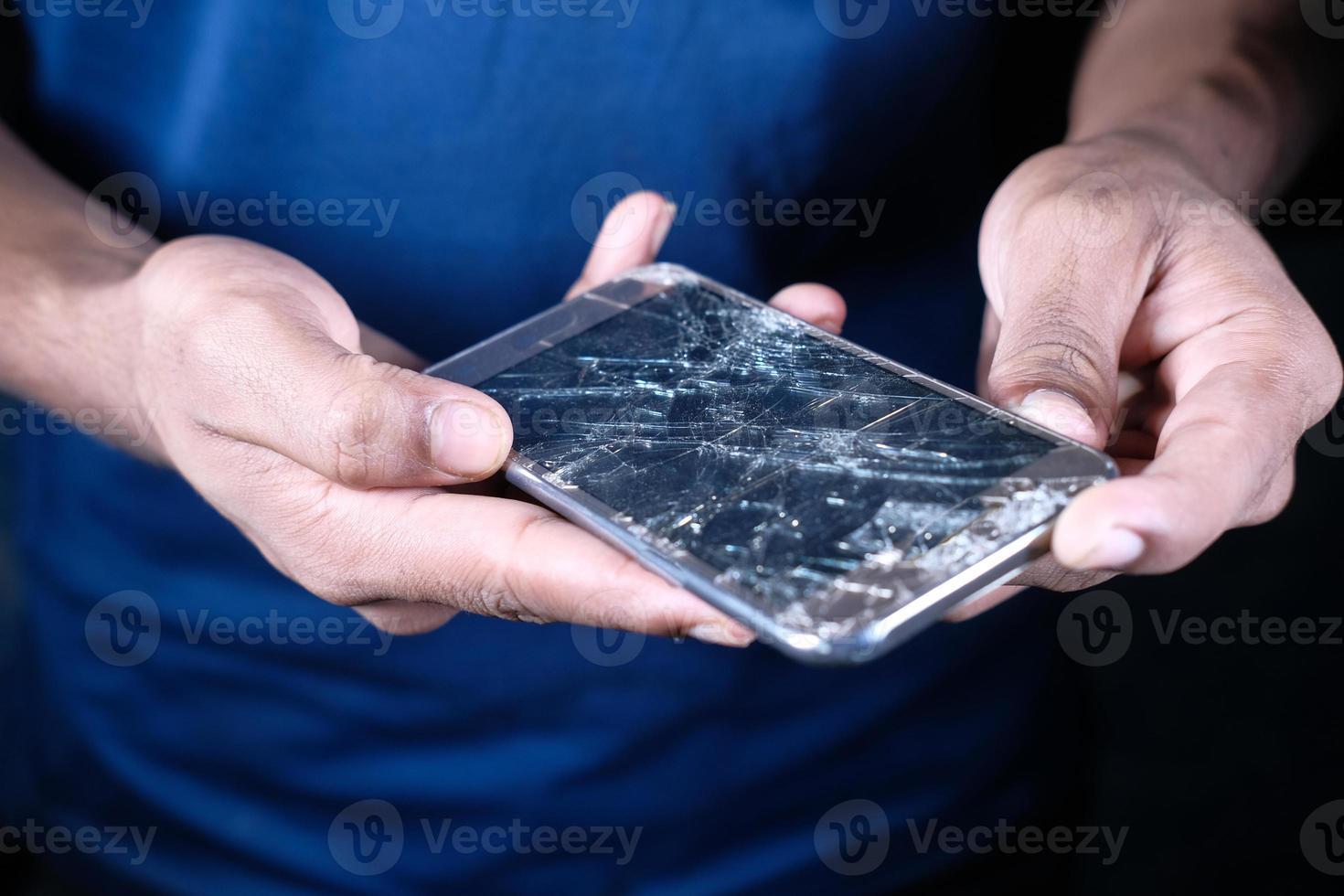 Stretta di mano dell'uomo che tiene telefono astuto rotto foto