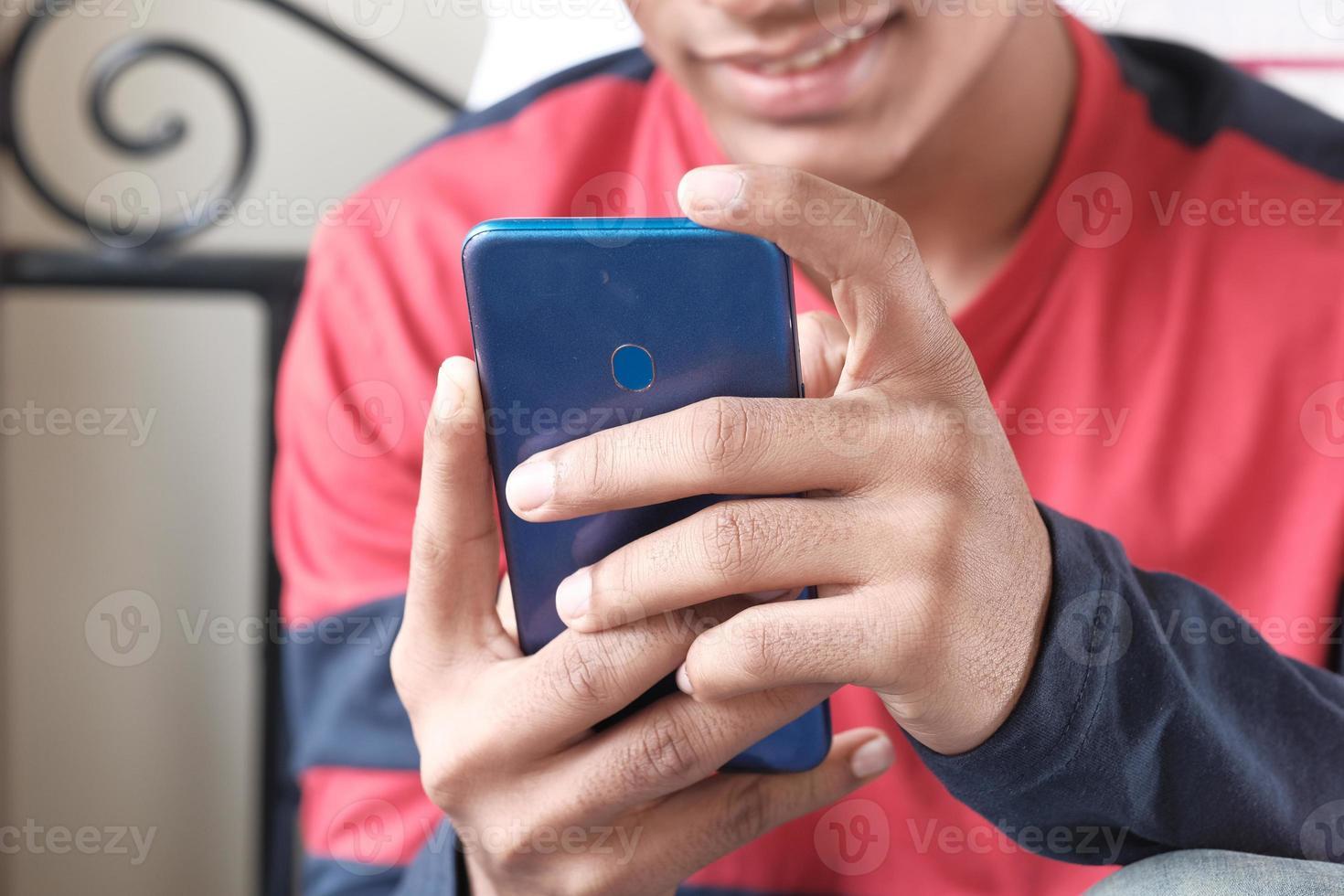uomo che per mezzo di un telefono intelligente foto