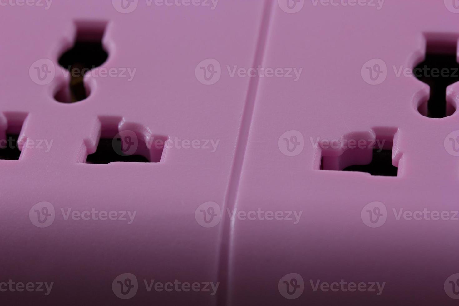 immagine da vicino di una presa rosa isolata su fondo nero foto