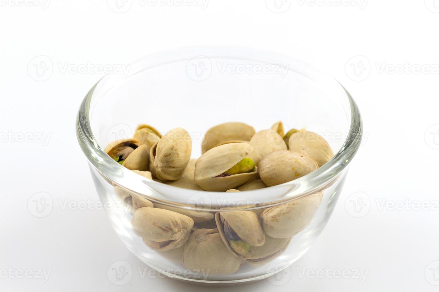 pistacchi in una lastra di vetro, isolato su sfondo bianco foto