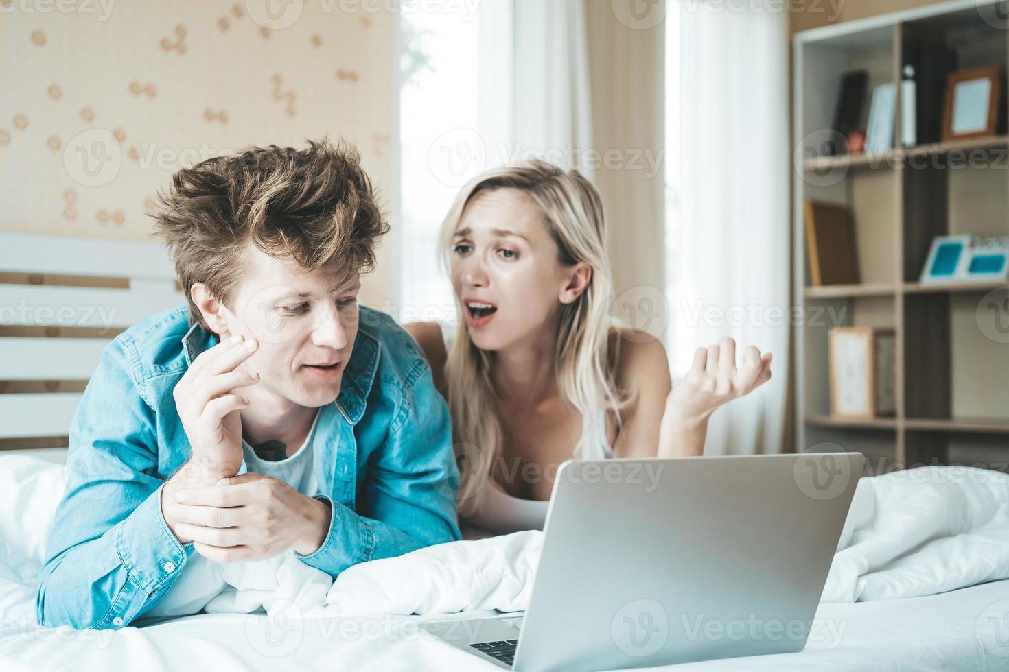 coppia felice utilizzando il computer portatile sul letto foto