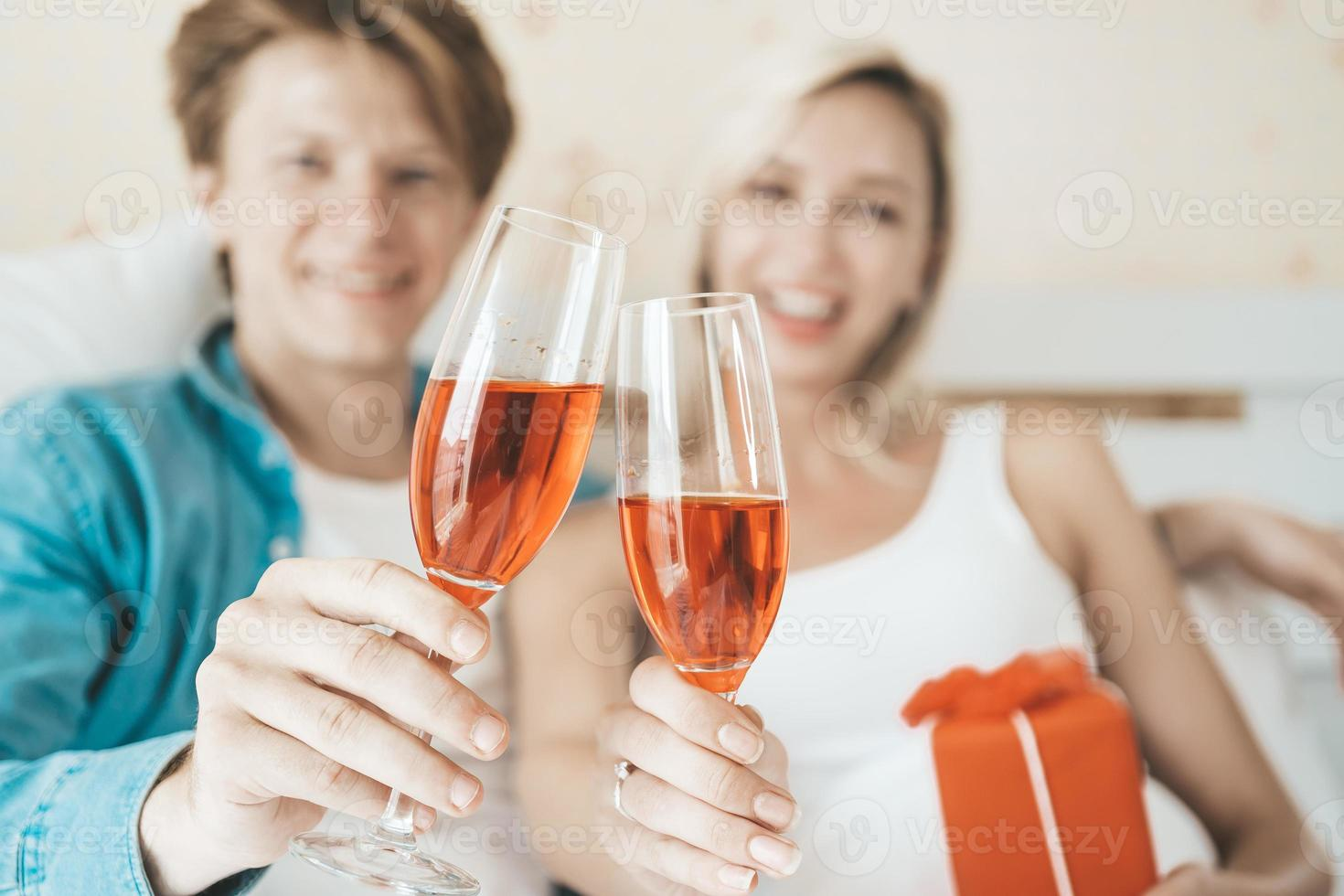 coppia felice che beve vino in camera da letto foto