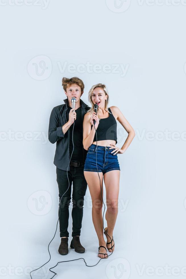 felice ritratto di coppia in possesso di microfoni e canto foto